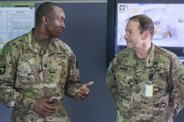 Lt. Col. Mike Jordan (left), commander, Army Field Support Battalion-Kuwait, talks with Maj. Gen. Edward Dorman, J-4 (logistics), U.S. Central Command about Army Prepositioned Stocks-5 readiness and how quickly the 401st Army Field Support Brigade can issue equipment during a tour of an APS-5 warehouse at Camp Arifjan, Kuwait, July 20. (U.S. Army Photo by Justin Graff, 401st AFSB Public Affairs)