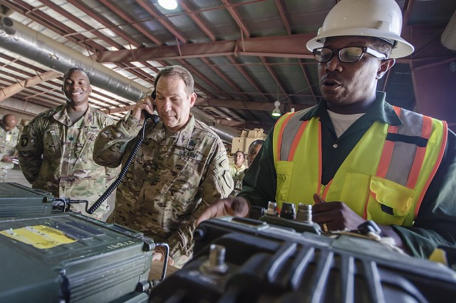 Maj. Gen. Edward Dorman (center), J-4 (logistics), U.S. Central Command, jokingly answers an unplugged radio unit that was on a display table featuring combat enablers, drawing laughter and lightening the mood during a tour of an Army Prepositioned Stocks-5 warehouse at Camp Arifjan, Kuwait, July 20. (U.S. Army Photo by Justin Graff, 401st AFSB Public Affairs)
