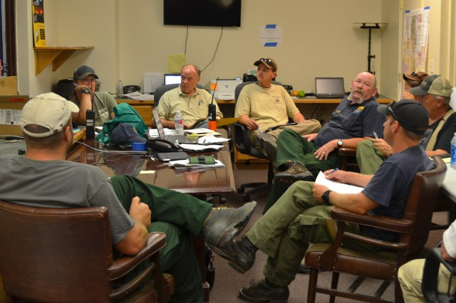 Incident Commander Jeff Sanocki (lower right) listens to reports from members of the Northern Utah Type 3 Incident Management Team about firefighting efforts in the Onaqui Mountain Complex. The team arrived at Dugway Proving Ground, July 17, bringing with it the ability to mobilize, coordinate, support and control large teams of firefighters. The fire burned nearly 38,000 acres. Photo by Robert Saxon, Dugway Proving Ground Public Affairs.