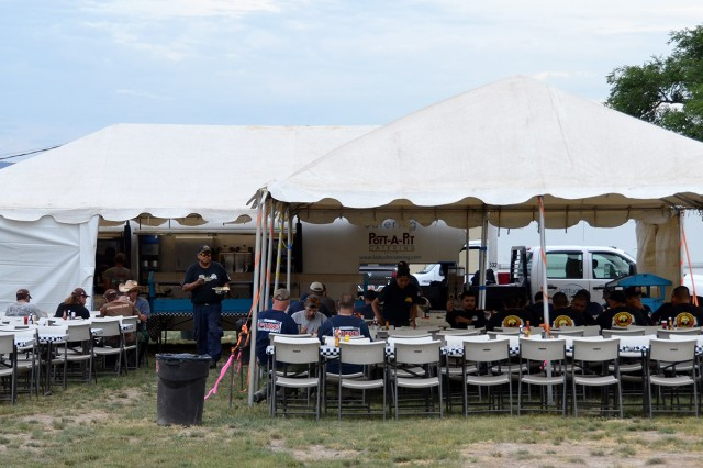 Firefighters eating their evening meal at the basecamp dining facility set up on Dugway Proving Ground. The basecamp and support operations, at their peak, comprised nearly 550 personnel, more than 275 of whom were firefighters. The fire burned nearly 38,000 acres. Photo by Robert Saxon, Dugway Proving Ground Public Affairs.