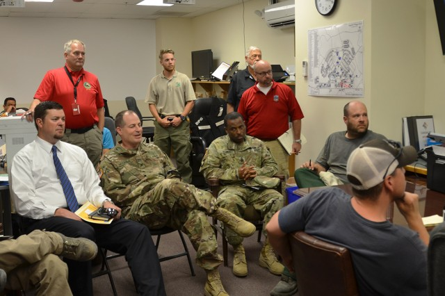 (L to R): Dugway's Aaron Goodman, garrison manager, Col. Brant Hoskins, commander, and Command Sgt. Maj. Joe Bonds, command sergeant major, listen to a daily brief at the incident command post about firefighting efforts in the Onaqui Mountain complex. Photo by Robert Saxon, Dugway Proving Ground Public Affairs.