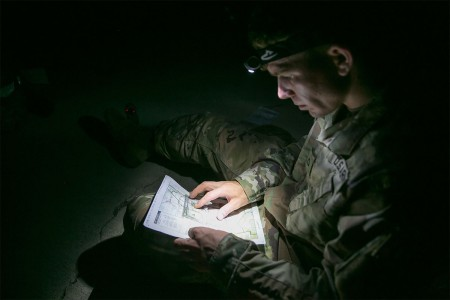 Pfc. Robert Nelson assigned to 687th Rapid Port Opening Element, determines the grid coordinate of a point on a map during night land navigation at the 2017 Army Materiel Command's Best Warrior Competition, July 18, 2017, at Camp Atterbury, Ind. During the three-day competition, these elite warriors are test on basic and advanced warrior tasks and drills.