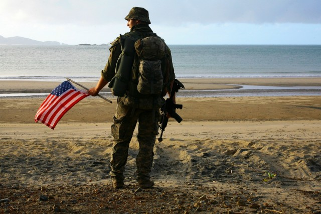 Spc. Shawn Spafford, an infantryman assigned to Charlie Troop, 2nd Squadron, 101st Cavalry Regiment of the New York Army National Guard, poses with an American Flag on the beach occupied by his troop during exercise Talisman Saber, July 14, 2017 at Shoalwater Bay, Queensland, Australia. During the exercise, a series of war games, New York Army National Guard Soldiers fought against, and alongside Australian and New Zealand personnel.