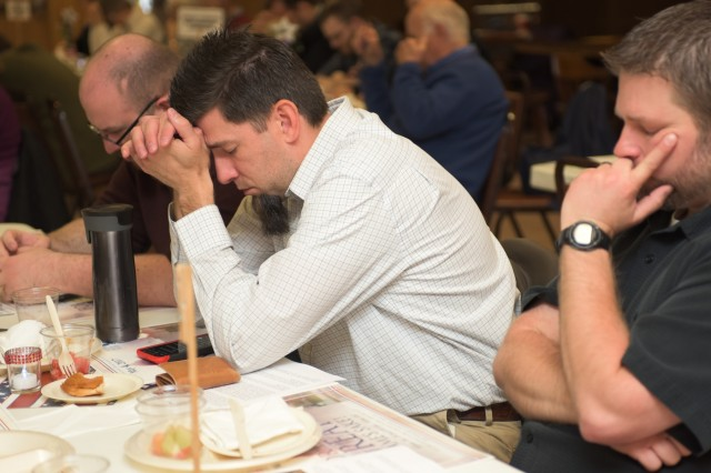 Three clergy members bow their heads in prayer during the Mayor's Prayer Breakfast held at the Geneseo Moose Lodge in Geneseo, Ill., May 4, 2017. About 50 clergy members, civic leaders and local residents attended the event, sharing a meal and praying for local, state and national government; emergency personnel; schools; and the nation's military.
