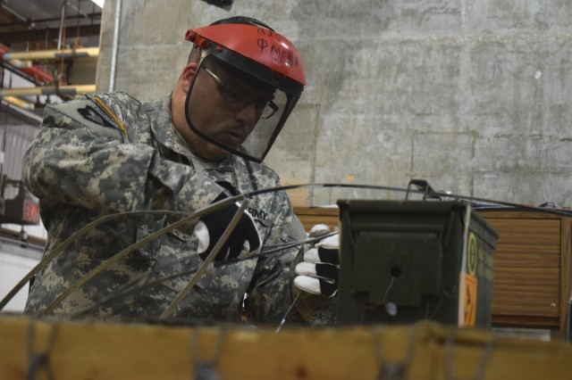A Soldier from the 221st Ordnance Company inspects gear and small arms and prepares them for transport and storage at Crane Army Ammunition Activity. The Soldiers of the 221st are receiving valuable experience handling munitions to increase mission readiness.