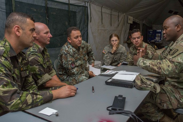 The Saber Guardian 17 MASCAL Communications team discusses how to achieve interoperability between their radio and communications systems July 13, 2017. Communications systems were ultimately synced utilizing a Tactical Voice bridge which allows syncing different radio systems without compromising the security keys of different radio systems.
