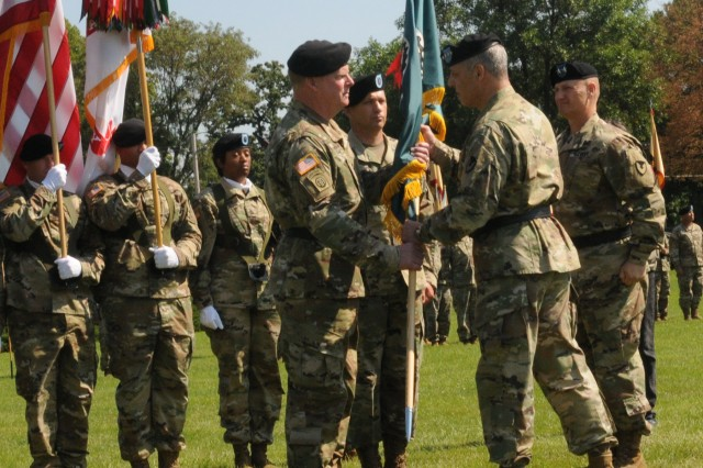 Gen. Gustave F. Perna, right, commander, Army Materiel Command, passes the unit colors to Maj. Gen Duane A. Gamble, left, to signify him as the leader of the Army Sustainment Command, during the Change of Command Ceremony held on Rock Island Arsenal, July 25. Outgoing commander, Maj. Gen. Edward M Daly, stands at attention, following his relinquishment of command.
