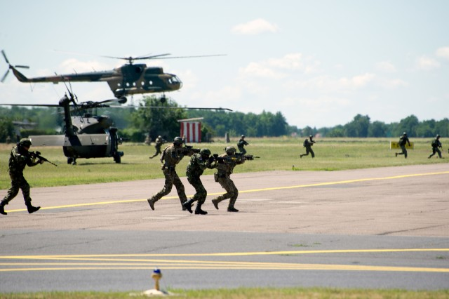Special operations forces from the U.S., Hungary, Romania, Slovenia, and Croatia assault a building from U.S. Army UH-60 helicopters from the 10th Combat Aviation Brigade, while Hungarian SOF fast rope from a Hungarian Mi-8 (Hip) Multirole Medium-Lift Helicopter July 12 during exercise Black Swan in Szolnok, Hungary. Black Swan was a Hungarian-led special operations forces exercise from June 26 -- July 22, 2017 across locations in Bulgaria, Hungary and Romania and included participants from over eight countries. Paratroopers from the U.S. Army's 173rd Airborne Brigade and 10th Combat Aviation Brigade also participated in the exercise alongside the 20th Special Forces Group (Airborne) to improve integration between SOF and conventional forces across NATO Allies.