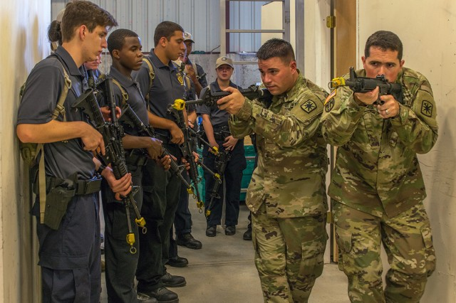 Instructors with the 14th MP Brigade demonstrate proper room clearing techniques to explorers during the Bi-Annual National Law Enforcement Explorers Academy July 19. Thirty explorers ages 14 to 20 experienced what it's like to be a Soldier in the Military Police Corps.