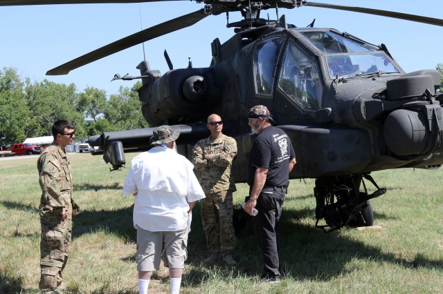 Chief Warrant Officer 2 Anthony Manfredi, left, and Chief Warrant Officer 2 Brandon Vanmeter, right, with Company A, 1st Aviation Reconnaissance Battalion, 1st Aviation Regiment, 1st Combat Aviation Brigade, 1st Infantry Division, talk to Vietnam veterans at the Kansas Veterans and Family Reunion on Veterans Point at El Dorado State Park in El Dorado, Kansas, July 21. The reunion was for veterans who had served, or currently serve, in any one of the nation's military branches. (Sgt. Jarrett E. Allen/1st CAB Public Affairs Office)