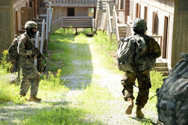 N.Y. Army National Guard Soldiers move through a village in a field training exercise, on the Camp Smith Training Site, Cortlandt Manor, N.Y., July 20, 2017. Soldiers were conducting room clearings and searching for enemies during a practical exercise to teach Soldiers how to take control of a situation, and practice order of succession. The training was part of the New York Army National Guard's Future Leaders Course, a pilot program aimed at preparing Soldiers to become NCOs.