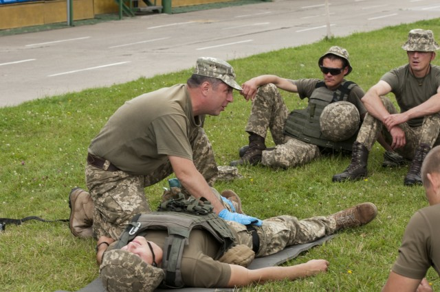 A Ukrainian Observer Coach Trainer with the Yavoriv Combat Training Center corrects a soldier from Ukraine's 1st Battalion, 95th Separate Airmobile Brigade in the proper application of a compression bandage during the first entirely Ukrainian-led combat first aid course at the Yavoriv CTC on the International Peacekeeping and Security Center near Yavoriv, Ukraine on 24 July.Yavoriv CTC OC/Ts, mentored by Soldiers from the U.S. Army's 45th Infantry Brigade Combat Team, led the training for soldiers from the 1st Battalion, 95th Separate Airmobile Brigade during the battalion's rotation through the Yavoriv CTC. The 45th is deployed to Ukraine as part of the Joint Multinational Training Group-Ukraine, an international coalition dedicated to improving the CTC's training capacity and building professionalism within the Ukrainian army. (Photo by Staff Sgt. Eric McDonough, 45th Infantry Brigade Combat Team)