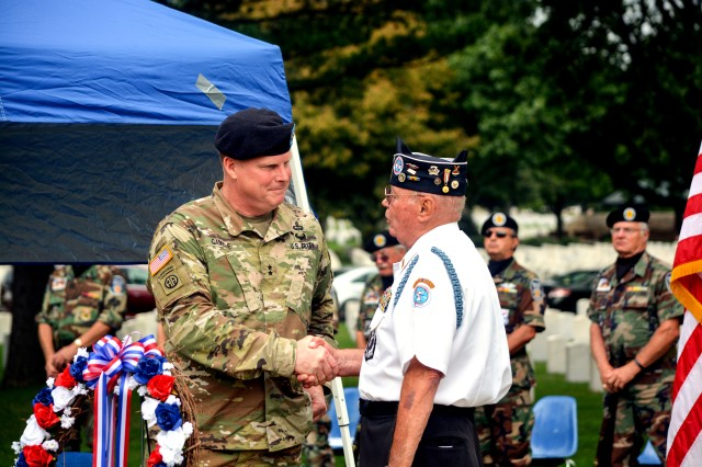 Maj. Gen. Duane Gamble, commander, U.S. Army Sustainment Command is welcomed by Ron Sears, president, Quad Cities Chapter #168 of the Korean War Veterans Association during a ceremony to honor Korean War veterans at Rock Island Arsenal National Cemetery, July 27.