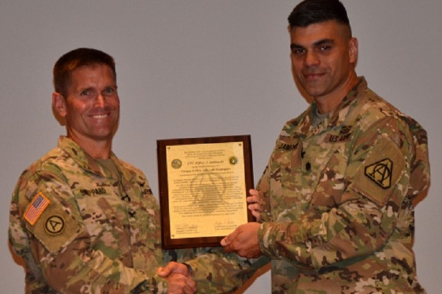 Col. Tal Sheppard, left, the Fixed Wing project manager, presents the Transport Aircraft product charter to Lt. Col. Jeffrey Jablonski in a ceremony July 26 at Bob Jones Auditorium.