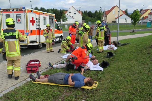First responders from the USAG Bavaria Fire Department asses and treat victims of a simulated active shooter during a full scale exercise held here July 15, 2017. The victims were played by volunteers from across the installation who donated their Saturday to help the garrison test the responses and standard operating procedures it would implement in the case of a real-world emergency. Disclaimer: All injuries are simulated.