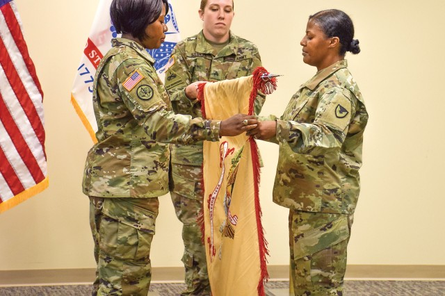 The command team of the 923rd Contracting Battalion at the Mission and Installation Contracting Command-Fort Riley (Kansas) including Lt. Col. Mary O.B. Drayton, left, and Sgt. Maj. Kimala Cox, right, unravel the unit colors during an uncasing of the colors ceremony July 20. The uncasing signifies the unit's reassignment and permanent change of station to Fort Riley from Warren, Michigan.