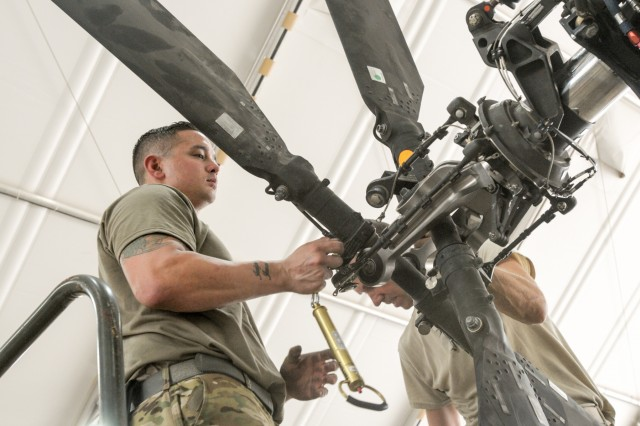 CAMP TAJI MILITARY COMPLEX, Iraq - Sgt. Johnathan Orbe an armament electrical avionic system repairer with the 449th Aviation Support Battalion, 29th Combat Aviation Brigade, works on attaching the tail rotor blades on the AH-64E Apache helicopter during the 500-hour Phase Maintenance cycle at Camp Taji Military Complex, Iraq, July 6, 2017. Proper maintenance ensures that the AH-64E Apache continues to provide reconnaissance and attack capability in the fight against ISIS for Combined Joint Task Force - Operation Inherent Resolve. CJTF-OIR is the global Coalition to defeat ISIS in Syria and Iraq.