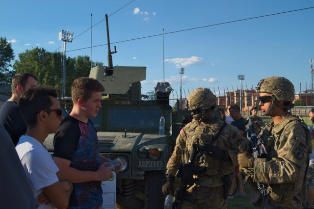 US Army Pfc. Daniel Davis (left) and Pfc. Zachary Dennis (right), both gunners with the 110th Military Police Company, currently assigned to the Regimental Engineering Squadron, 2nd Cavalry Regiment, discuss their work with Macedonian citizens during a static display at Stip, Macedonia on July 30, 2017. The Regimental Engineering Squadron is currently in country as a part of Dragoon Guardian, an offshoot of Operation Atlantic Resolve, which is a NATO mission involving the US and Europe in a combined effort to strengthen bonds of friendship and to deter aggression. (Photo by Army Pfc. Nicholas Vidro, 7th Mobile Public Affairs Detachment)