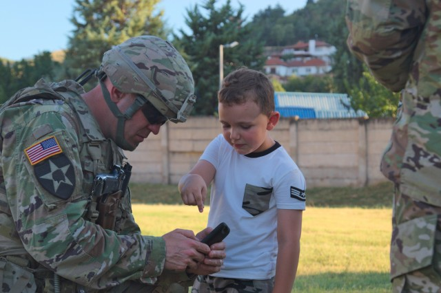 US Army Lt. Col. Mark Himes, commander of the Regimental Engineering Squadron, 2nd Cavalry Regiment, shares his phone with a local Macedonian child during a static display at Stip, Macedonia on July 30, 2017. The 2nd Cavalry Regiment is currently driving by convoy through Macedonia as a part of Dragoon Guardian, an offshoot of Operation Atlantic Resolve, which is a NATO mission involving the US and Europe in a combined effort to strengthen bonds of friendship and to deter aggression. (Photo taken by Pfc. Nicholas Vidro, 7th Mobile Public Affairs Detachment.)