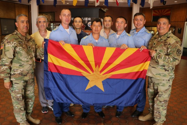 Command Sgt. Major Fidel Zamora, the senior enlisted advisor for the Arizona Army National Guard and Command Sgt. Major Saul Garcia, the command sergeant major for the 98th Aviation Troop Command, hold the Arizona state flag with delegates from Kazakhstan during a visit to exchange aviation maintenance practices and non-commissioned officer development July 25. The visit came within weeks of the U.S. government's formal renewal of its partnership with Kazakhstan, extending the 24-year-old legacy of cooperation for five more years.