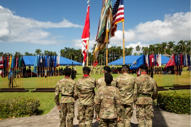 The 130th Engineer Brigade Color Guard team (foreground), under the direction of Pacific Ocean Division's Command Sgt. Maj. Yolanda Tate, is set to post the Colors at a ceremony, July 27, at historic Palm Circle, Fort Shafter, Hawaii.  The official party, in the background, stands at parade rest, while they await the cue to begin the change of command ceremony, when Col. Thomas J. Tickner becomes the 33rd commander of the Pacific Ocean Division, U.S. Army Corps of Engineers.