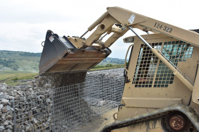 Spc. Alvin Stevens pours rock into Gabion baskets from his Skidsteer loader.  These Gabion baskets will support moving targetry at a tank range at Joint National Training Center, Cincu, Romania. Spc. Stevens is a South Carolina Army National Guard Soldier with the 1223rd Engineer Company, 178th Engineer Battalion, currently serving in Romania as part of Resolute Castle 17, an operation which builds relationships with the NATO alliance and enhances its capacity for joint training and response to threats within the region.