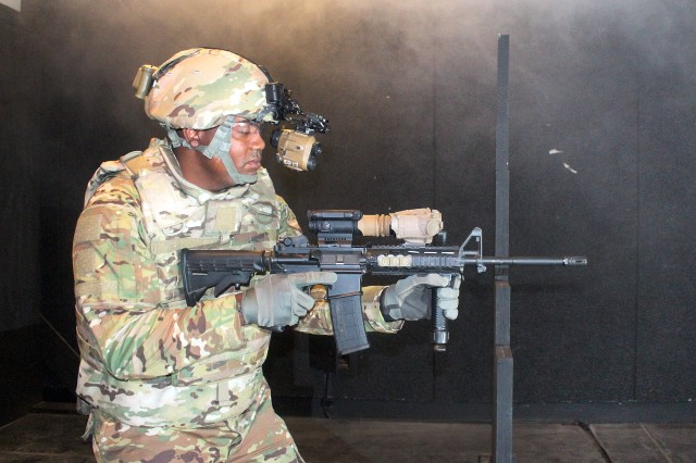 MAster Sgt. Lashon Wilson, the senior enlisted adviser for Product Manger Soldier Maneuver Sensors, demonstrates the use of the Enhanced Night Vision Goggle III, paired with a Family of Weapons Sights-Individual, at Fort Belvoir, Virginia, July 27, 2017.