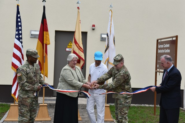 (Far Right) Installation Management Command-Europe Director Michael Formica and (Far Left) IMCOM Command Sgt. Maj. Ulysses Rayford hold the ribbon while (inside right) U.S. Army Garrison Rheinland-Pfalz Commander Col. Keith Igyarto and (inside left) USAG RP Deputy to the Commander Deborah Reynolds and (middle) Merida Hicham, German canteen contract lease holder, cut the ceremonial ribbon to open the new canteen for business, Aug. 1. Hicham, who formerly worked at the Rhine Ordnance Barracks canteen, brings his expertise to serve the Sembach community.