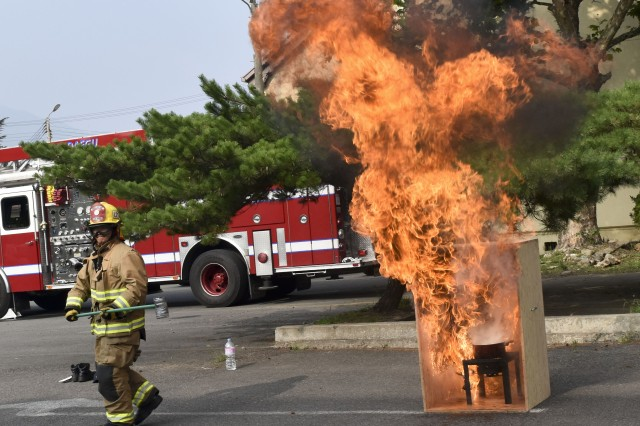 A firefighter demonstrates how dangerous it is to pour water into the frying oil pot, July 12 at the barracks on Camp Henry.