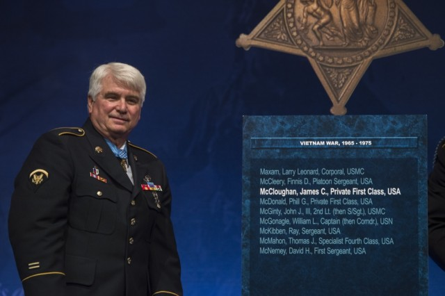 Spc. 5 James C. McCloughan stands by his just-unveiled Medal of Honor Hall of Heroes plaque during a ceremony Aug. 1, 2017, at the Pentagon in Washington, D.C. McCloughan distinguished himself during 48 hours of close-combat fighting against enemy forces May 13 to 15, 1969. At the time, then-Pfc. McCloughan was serving as a combat medic with Company C, 3rd Battalion, 21st Infantry, 196th Light Infantry Brigade, Americal Division, in the Republic of Vietnam.