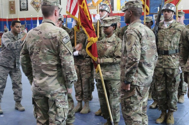 Incoming 595th Transportation Brigade Command Sergeant Major, Command Sgt. Maj. Denise Fisher, receives the command colors from Brigade Commander, Col. J Bradley Swift, accepting responsibility for the brigade