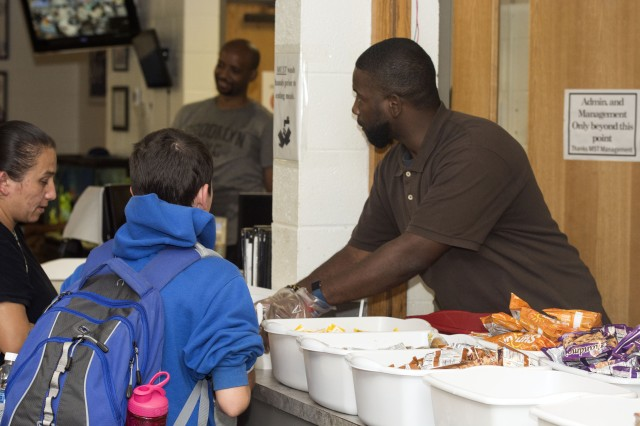 Corey Dwyer, the Assistant Director of Scales Child Development Center, hands out food.