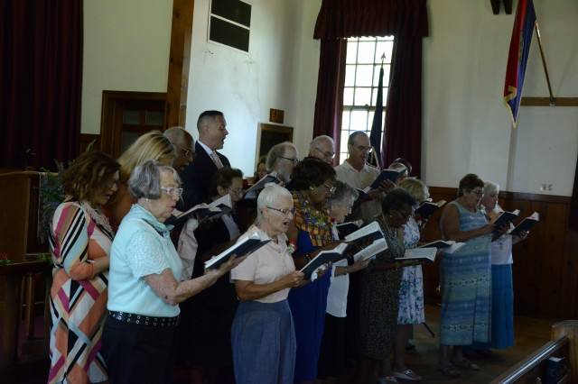 Parishioners celebrate the final service of Memorial Chapel July 30. The chapel, which is too costly to maintain and doesn't meet mission requirements, is set for demolition as part of an Army directive to remove all World War II era buildings on post.