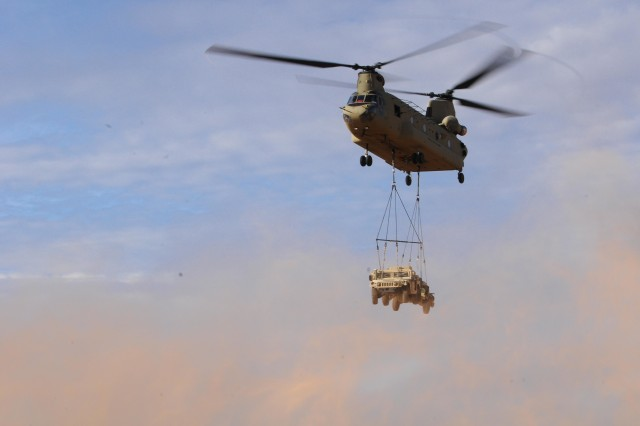 A CH-47 Chinook transports a Humvee during a sling-load operation as part of the Network Integration Evaluation (NIE) 17.2 at Fort Bliss, Texas, July 24, 2017.