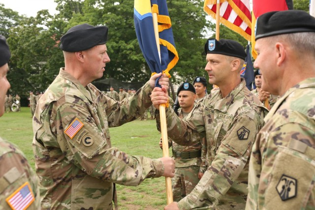Brig. Gen. Frederick R. Maiocco Jr., left, hands the 7th Mission Support Command unit guidon over to Command Sgt. Maj. Raymond Brown, right, during the 7th Mission Support Command change of command ceremony Aug. 4, 2017 on Daenner Kaserne in Kaiserslautern, Germany. Observing is Brig. Gen. Steven Ainsworth, foreground right, the outgoing commanding general, and Maj. Gen. Steven Shapiro, foreground left, commanding general of the 21st Theater Sustainment Command, 7th MSC's higher headquarters.