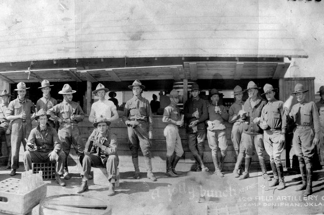 "First Lieutenant Harry Truman (14th from left) enjoying a soft drink with fellow officers, ""A jolly bunch at the 129 Field Artillery Canteen, Camp Doniphan, Oklahoma."" After the National Guard was drafted into the U.S. Army on August 5, 1917, Soldiers mustered at their home stations and mobilized into several training camps across the United States prior to their deployment to Europe. (Courtesy of Harry S. Truman Library & Museum)"