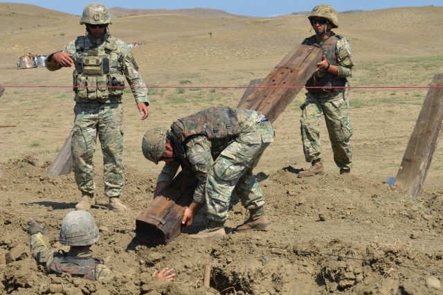 VAZIANI TRAINING AREA, Georgia - Soldiers of the 1st Engineer Sapper Company, Engineer Brigade, of the Georgian Armed Forces, place lumber at angles in the earth to create a defensive barrier, Vaziani Training Area, Georgia, Aug. 6, 2017. Soldiers of the 500th Engineer Support Company, 15th Engineer Battalion, 18th Military Police Brigade, 21st Sustainment Theater Command, Grafenwoehr, Germany, dig the ditches with the High Mobility Engineer Excavator (Hmee-I) prior. Together, the two units combine experience and skills to establish an engagement area to deter enemy forces, in Exercise Noble Partner. Noble Partner is a multinational U.S. Army Europe-led exercise conducting home station training for the Georgian light infantry company designated for the NATO Response Force. (U.S. Army photo by Sgt. Shiloh Capers)