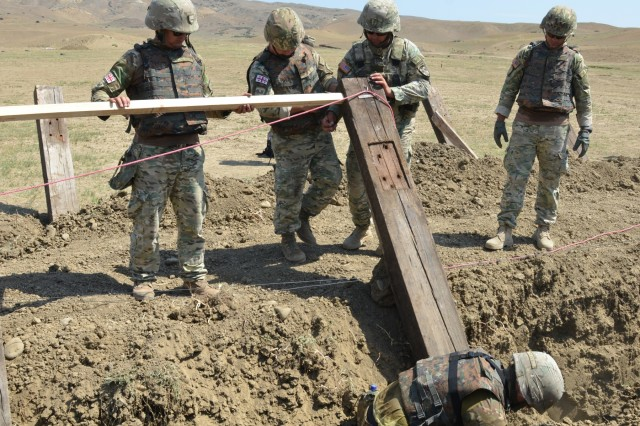 VAZIANI TRAINING AREA, Georgia - Soldiers of the 1st Engineer Sapper Company, Engineer Brigade, of the Georgian Armed Forces, measure the distance between lumber for proper placement of the obstacles in the company-sized engagement area, at Vaziani Training Area, Georgia, Aug. 6, 2017. The 500th Engineer Support Company (ESC), 15th Engineer Battalion, 18th Military Police Brigade, 21st Sustainment Theater Command, Grafenwoehr, Germany, digs the ditch with a High Mobility Engineer Excavator (HMEE-I). The 500th ESC participates in Exercise Noble Partner, a multinational U.S. Army Europe-led exercise conducting home station training for the Georgian light infantry company designated for the NATO Response Force. (U.S. Army photo by Sgt. Shiloh Capers)
