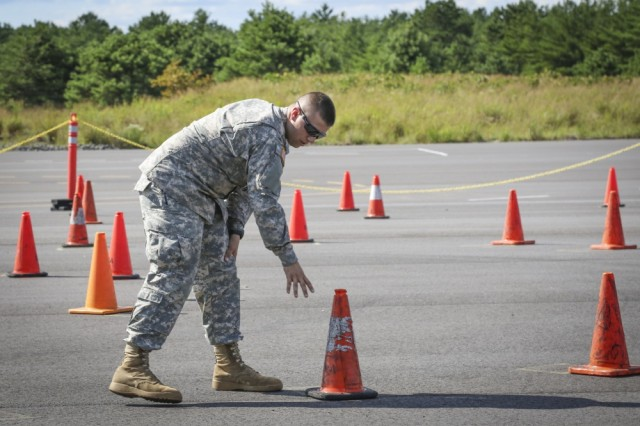 Army Reserve Spc. Dylan Torkelson, a military police Soldier assigned to the provost marshal's office, 335th Signal Command (Theater), sets up cones on a challenging Emergency Vehicle Operators Course at Joint Base McGuire-Dix-Lakehurst, New Jersey, Aug. 5. Torkelson was among a group of eight Soldiers from the 335th SC (T), who spent two days acquiring and honing their emergency vehicle driving skills in the course.