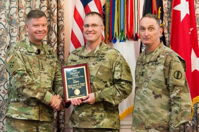 (Left to right) Gen. David Perkins, U.S. Army Training and Doctrine Command commanding general, Maj. Jason Nagel, and Command Sgt. Maj. David Davenport, Sr., TRADOC command sergeant major, pose for photographs at the TRADOC 2016 Instructor of the Year Awards ceremony at Fort Eustis, Virginia, Aug. 3, 2017.  Nagel is assigned to the 11th Battalion, 95th Regiment, 97th Training Brigade, 100th Training Division, under the 80th Training Command.  He won the award in the Army Reserve category.