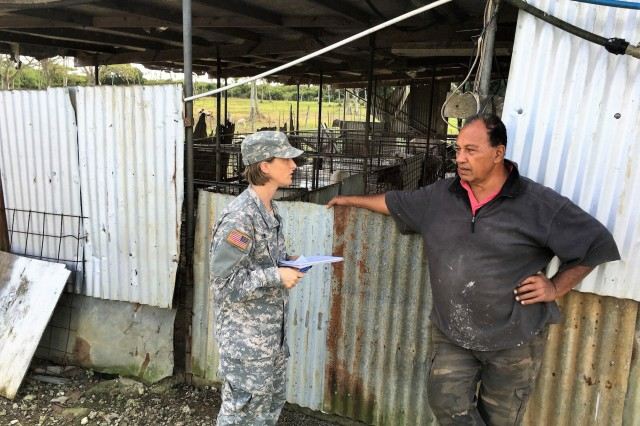Maj. Kimberly Yore (center), an Army vet from Joint Base Lewis-McChord in Washington state, interviews a farmer in front of his pig pen, in the Kingdom of Tonga, July 17, 2017.