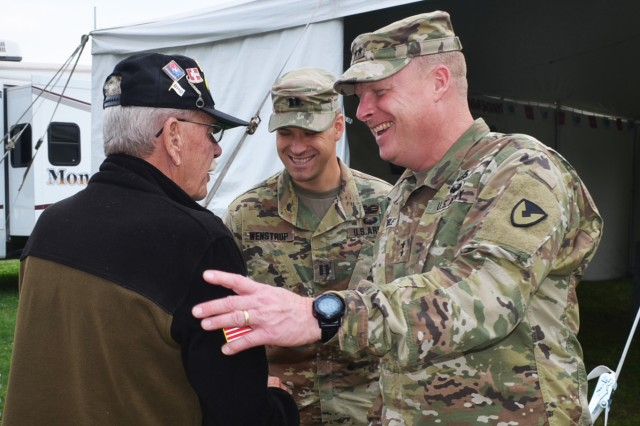 Maj. Gen. Duane Gamble, commanding general, U.S. Army Sustainment Command, meets with a ceremony attendee in the Veterans Tent during the Mississippi Valley Fair Aug. 5.
