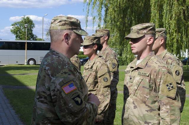 Gen. Mark Milley, U.S. Army Chief of Staff, asked Spc. Patrick Hilton, a motor transport operator with the 32nd Composite Truck Company, about his military background during a coin presentation at a Polish Military Air Base in Powidz, Poland, as part of his trip throughout Eastern Europe, Aug. 7, 2017. The distinguished visitors toured the Polish Air Base because of its strategic value, to get a better idea of what operations take place in Powidz, how the location might be utilized in the future, and to recognize U.S. Soldiers for their outstanding performance while deployed in support of Operation Atlantic Resolve.