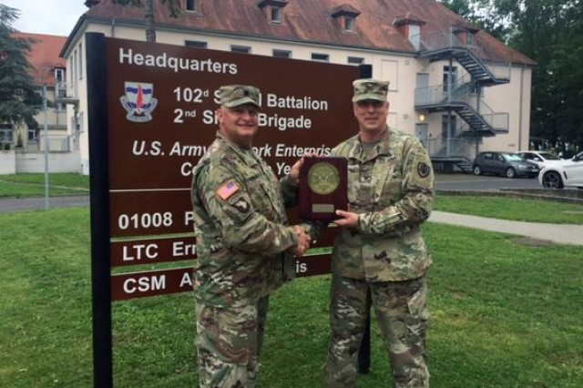 U.S. Army Col. Andrew McClelland (right), commander of Defense Information Systems Agency Europe, presents an award to Lt. Col. Ernest Tornabell IV, commander of the 102nd Strategic Signal Battalion, 2nd Theater Signal Brigade, Aug. 3, 2017, in front of the battalion's headquarters building in Wiesbaden, Germany. The Enterprise SATCOM Gateway-Landstuhl, 102nd Strategic Signal Bn., was named the DISA Europe 2016 European Gateway Facility of the Year in the Large Gateway category.