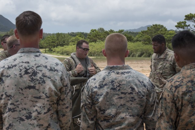 U.S. Army Aviation Battalion Japan Chief Warrant Officer 3 Jimmy Kafer, UH-60 Black Hawk pilot, briefs participants during a battalion collective training exercise July 31, 2017, in Okinawa, Japan. The exercise included the USAABJ, stationed at Camp Zama, Japan, and the 1st Battalion, 1st Special Forces Group (Airborne) stationed at Torii Station, Japan, involving cargo sling loading and parachute jump training. (U.S. Air Force photo/ Airman 1st Class Greg Erwin)