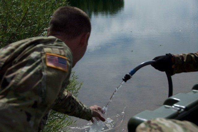 A Soldier Assigned to 10th Special Forces Group (Airborne) fills his water bottle from water treated by the Aspen 5500M, which is a small and mobile water treatment system, during a training exercise at a reservoir on Fort Carson, Colo. July 27, 2017. The training took place in order to field the Aspen 5500M and test its capabilities as well as that of the much larger Tactical Water Purification System. (US Army photo by Sgt. Brandon Franklin)