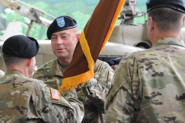 Col. Kelly E. Hines, U.S. Army Warrant Officer Career College commandant, assumes command from Col. Garry L. Thompson as he receives the unit colors from Brig. Gen. Troy D. Galloway, U.S. Army Combined Arms Center deputy commanding general, during a change of command ceremony at Fort Rucker, Ala., Aug. 4.