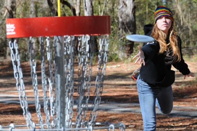 Stephanie Woodard, civilian, tosses a disc at one of the baskets on the disc golf course during a previous disc golf tournament at Fort Rucker.