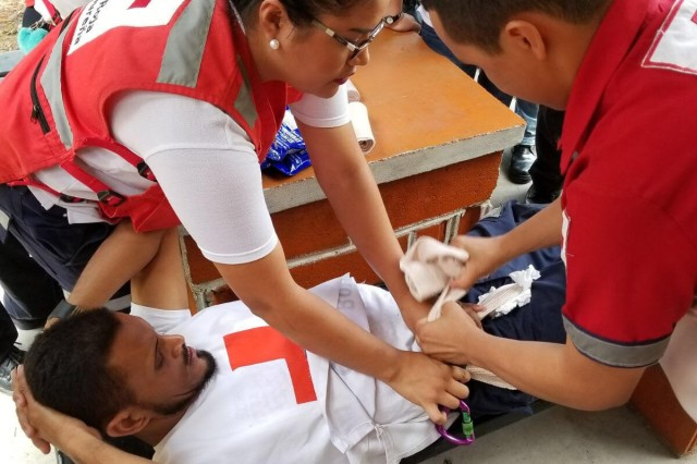 Members of the Honduran Red Cross participate in a hands-on practical exercise to stop inguinal bleeding during a four-hour pre-hospital training course July 22 in Tegucigalpa, Honduras.