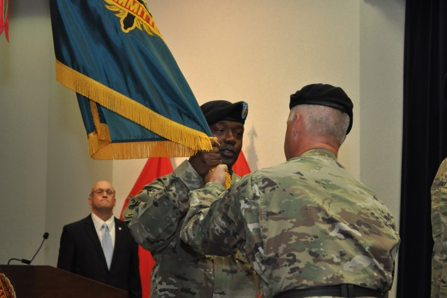 Brig. Gen. Paul Pardew, Expeditionary Contracting Command, commanding general, passes the ECC guidon to Command Sgt. Maj. Gerald A. Wright during an assumption of responsibility ceremony Aug. 11.Wright became ECC's fourth command sergeant major in the ceremony and he is the first contracting NCO, military occupational specialty code 51C, to hold a nominative command sergeant major position.